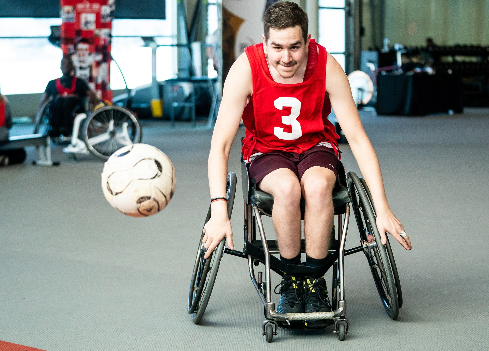 A Paralympian Search participant in a wheelchair races to catch a ball