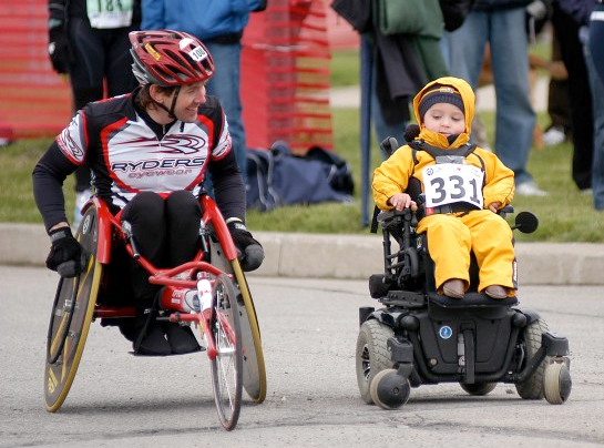 Image of Chris in a racing chair with a child in a motorized wheelchair