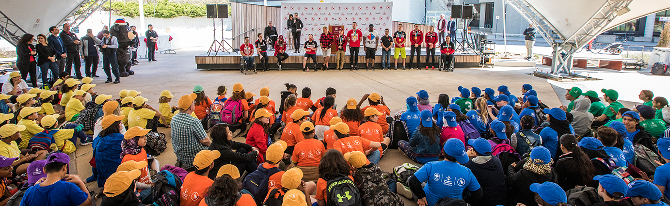 Kids in colourful Jumpstart shirts looking at a stage of Paralympians