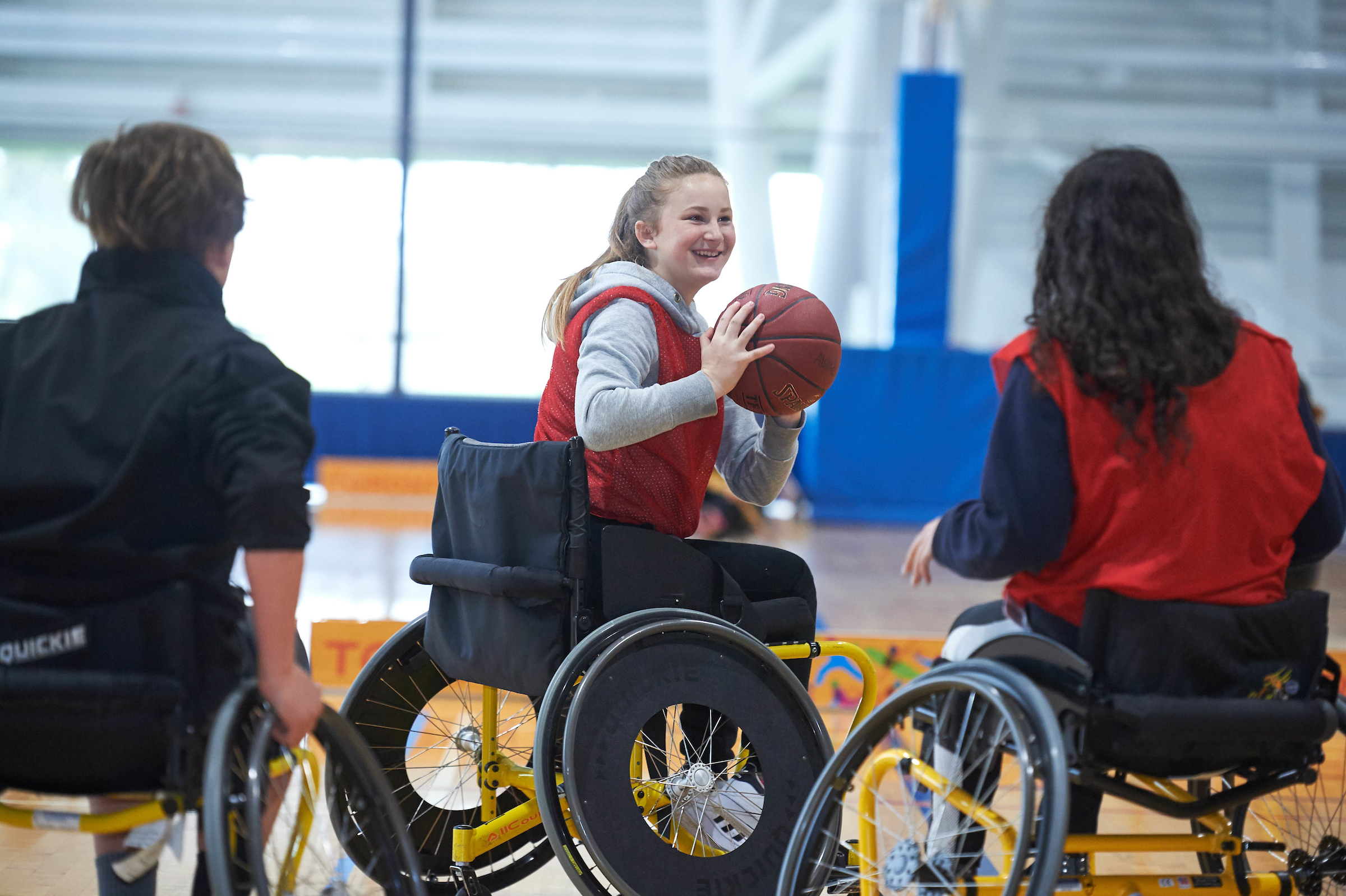 Teenage girl playing wheelchair basketball