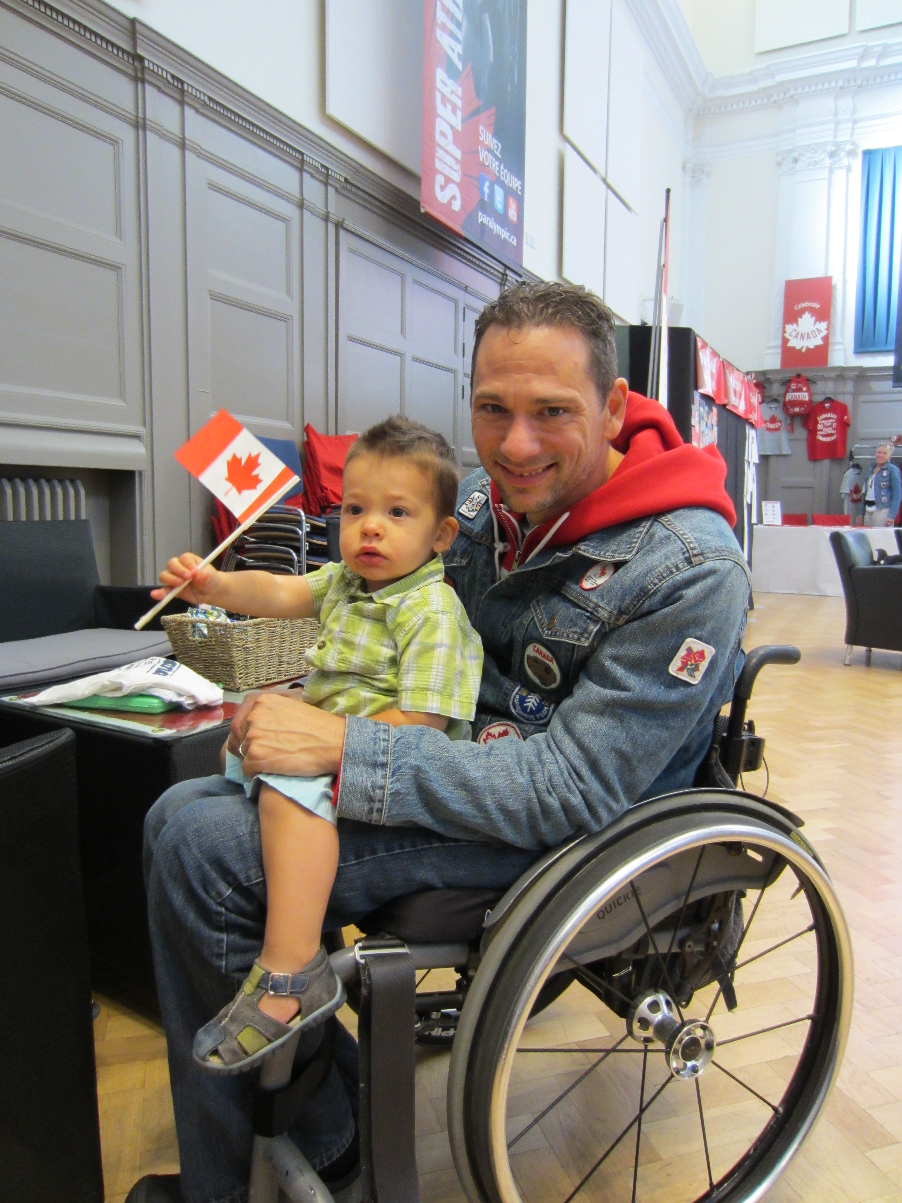 Man in a wheelchair with a kid on his lap
