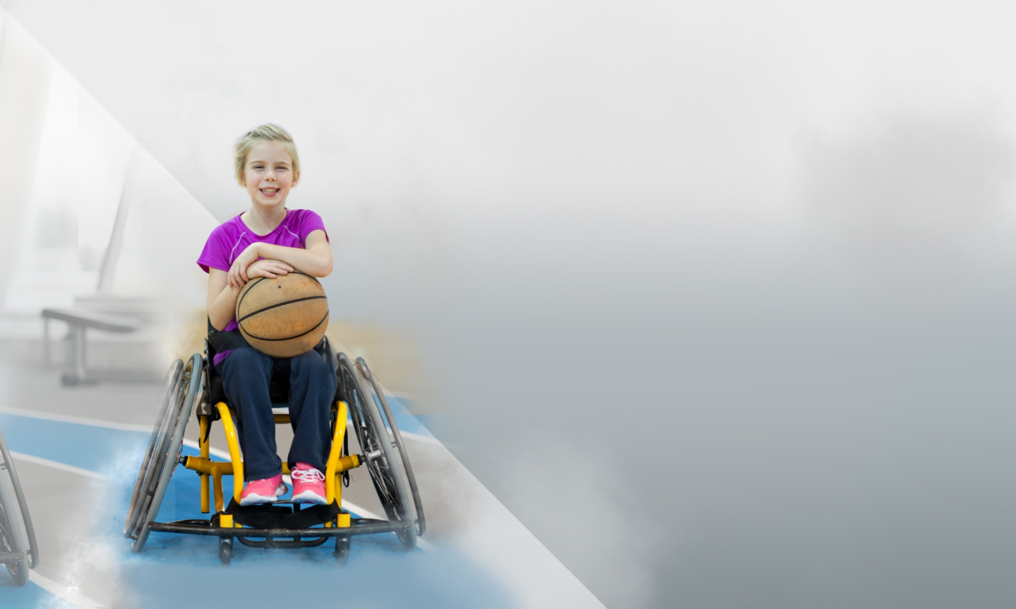 Girl in a wheelchair holding a basketball