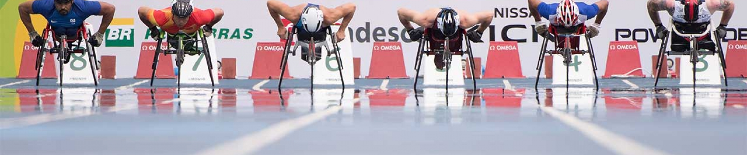 Racers line up in their wheelchairs at the 100m start line; 6 racers side by side in their lanes