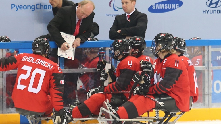 Paralympic hockey team getting advice from their coach.