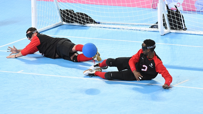 Goalball team stopping the ball from going into the net, players are laying down