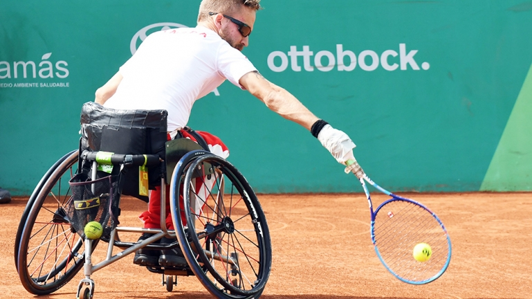 Rob Shaw reached from his chair low to ground for tennis ball