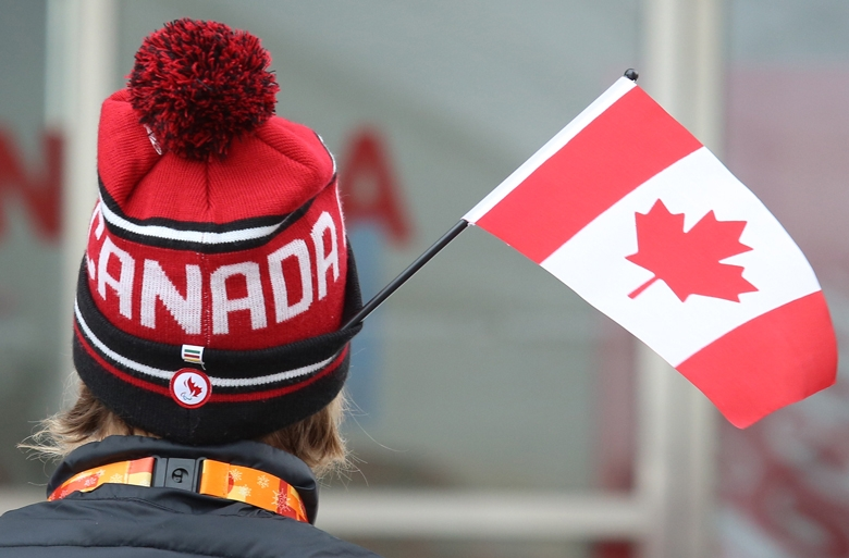 The back of a person's head wearing a Team Canada toque with a Canadian flag sticking out of the hat