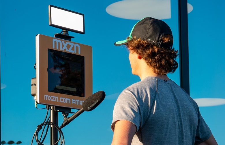 An athlete does an interview using MXZN Mixed Zone stations